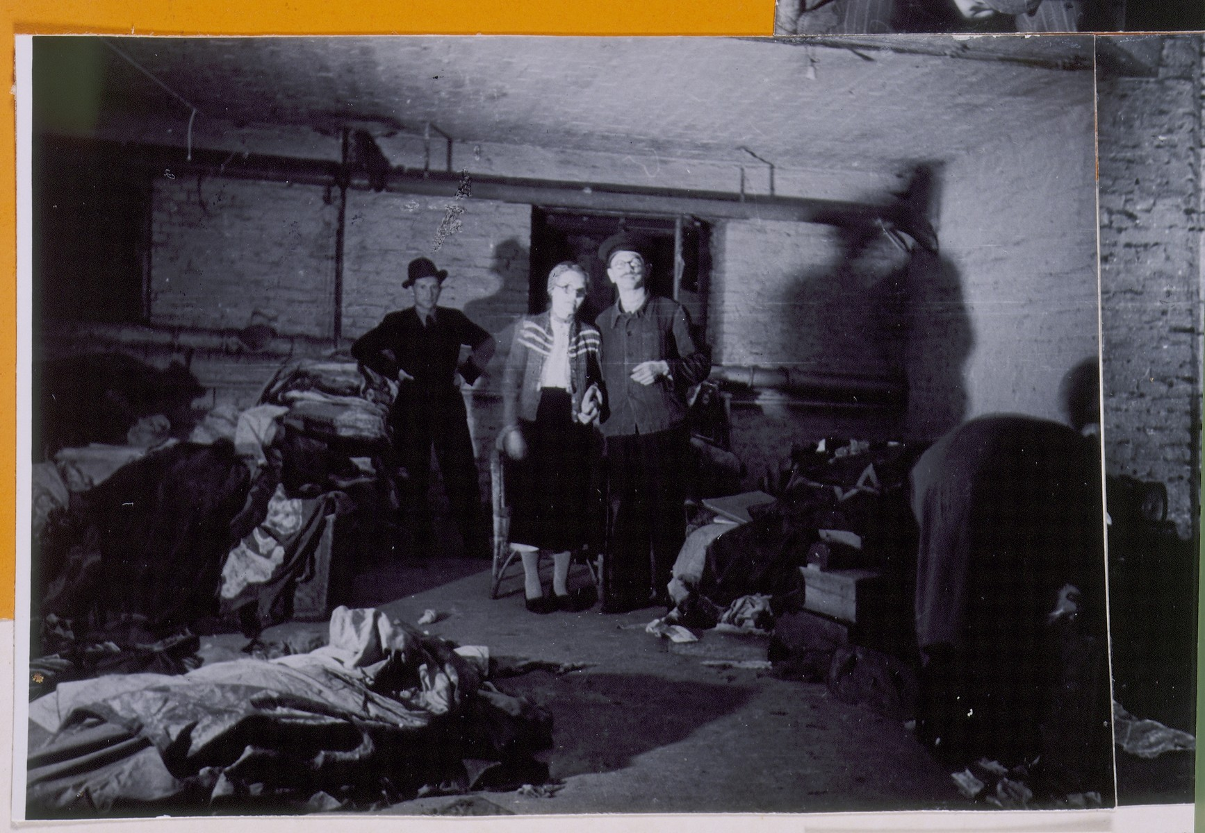 """Jewish survivors view a cellar storeroom in Berlin in which a stash of abandoned Torah scrolls was found.  The left-hand photograph on a page of a scrapbook/photo album bearing the title, """"Toras Hidden in Berlin and Found Again After the War.""""   The photo album was assembled by Pinkus Proszowski, a graphic designer, originally from Lodz, who served as director of the children's home in the Schlachtensee displaced persons camp."""