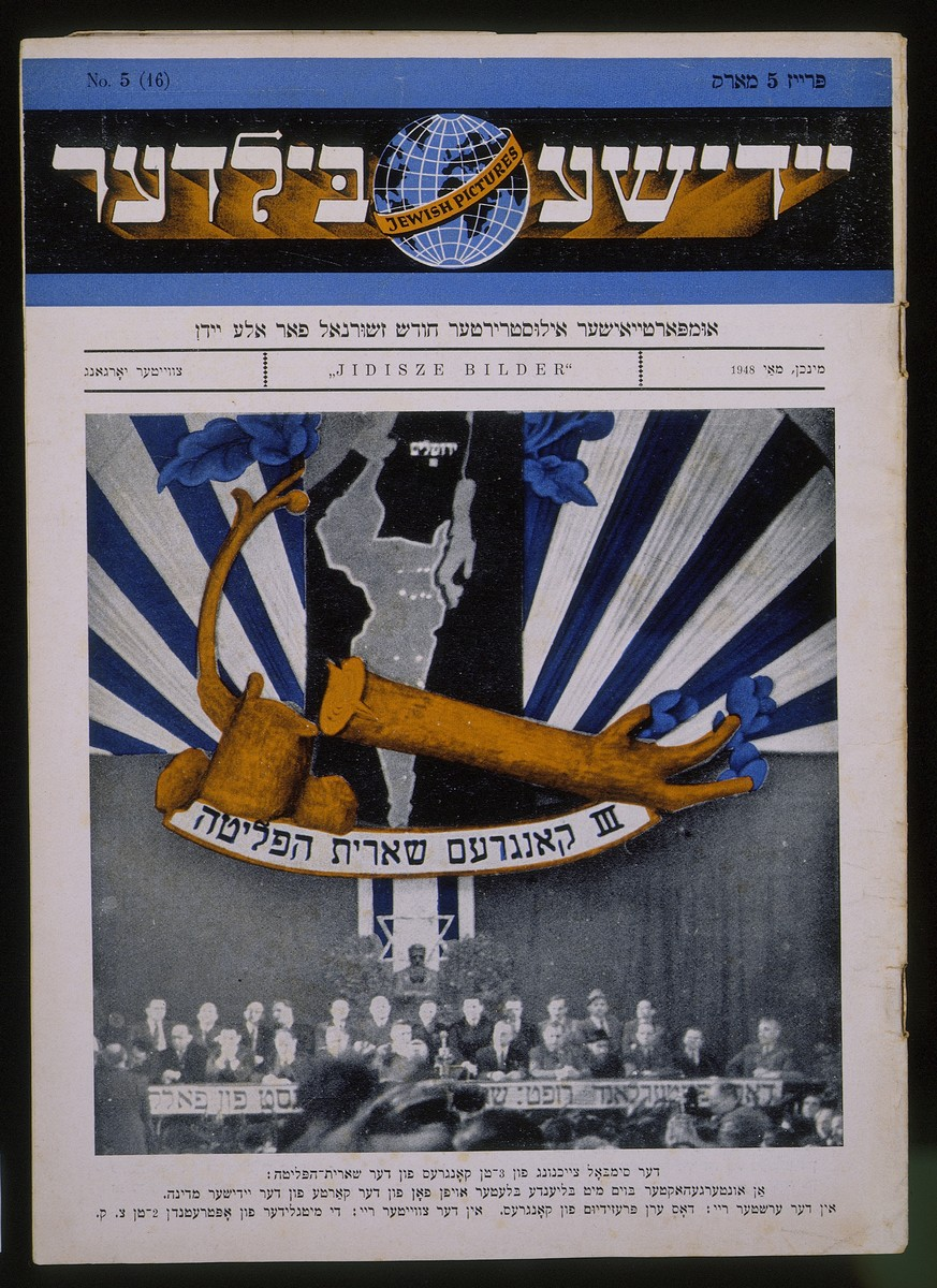 """Cover page of the publication """"Jidisze Bilder"""" [Jewish Photographs] with a photograph of participants at the Third Congress of the Shearit Ha-Pletah.  Above the participants is a graphic of a branch growing from a chopped down tree.  This became a symbol of the survivors."""