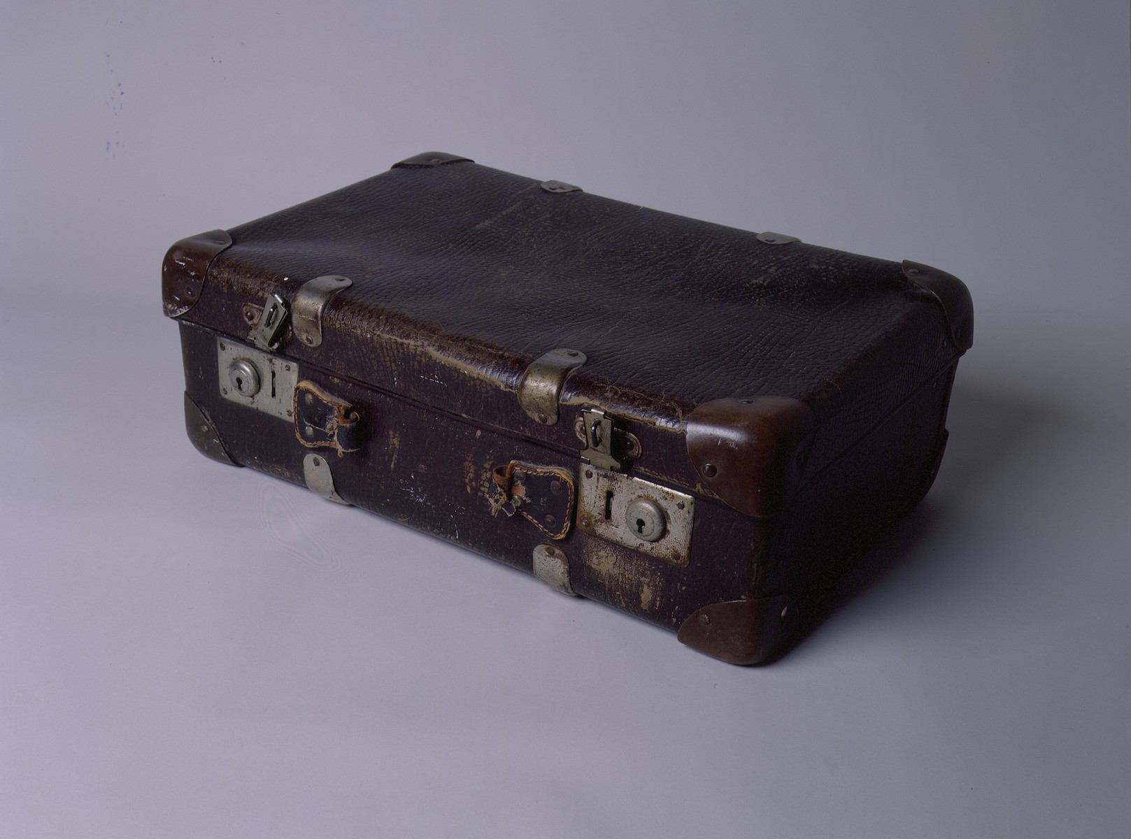 Small brown leather suitcase with metal clasps and corner reinforcements that was carried by the Leikachs, a family of Jewish survivors, from Poland to Italy.
