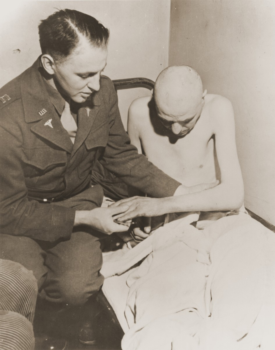 An American doctor examines a Soviet survivor at the Dortmund prisoner-of-war camp in Germany.