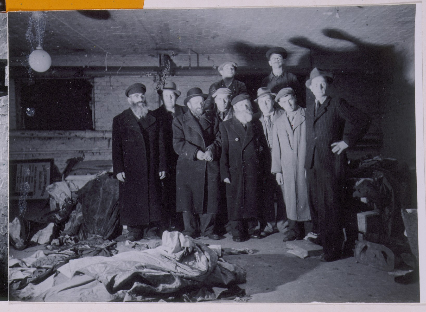 """Group portrait of Jewish survivors in a cellar storeroom in Berlin in which a stash of abandoned Torah scrolls was found.  The right-hand photograph on a page of a scrapbook/photo album bearing the title, """"Toras Hidden in Berlin and Found Again After the War.""""   The photo album was assembled by Pinkus Proszowski, a graphic designer, originally from Lodz, who served as director of the children's home in the Schlachtensee displaced persons camp."""