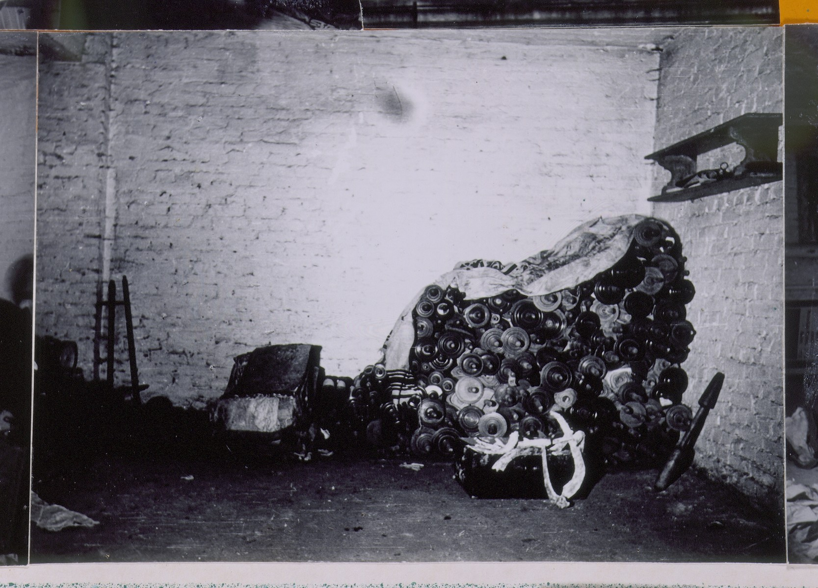 "Abandoned Torah scrolls are piled up in a cellar storeroom in Berlin.  The center photograph on a page of a scrapbook/photo album bearing the title, ""Toras Hidden in Berlin and Found Again After the War.""   The photo album was assembled by Pinkus Proszowski, a graphic designer, originally from Lodz, who served as director of the children's home in the Schlachtensee displaced persons camp."