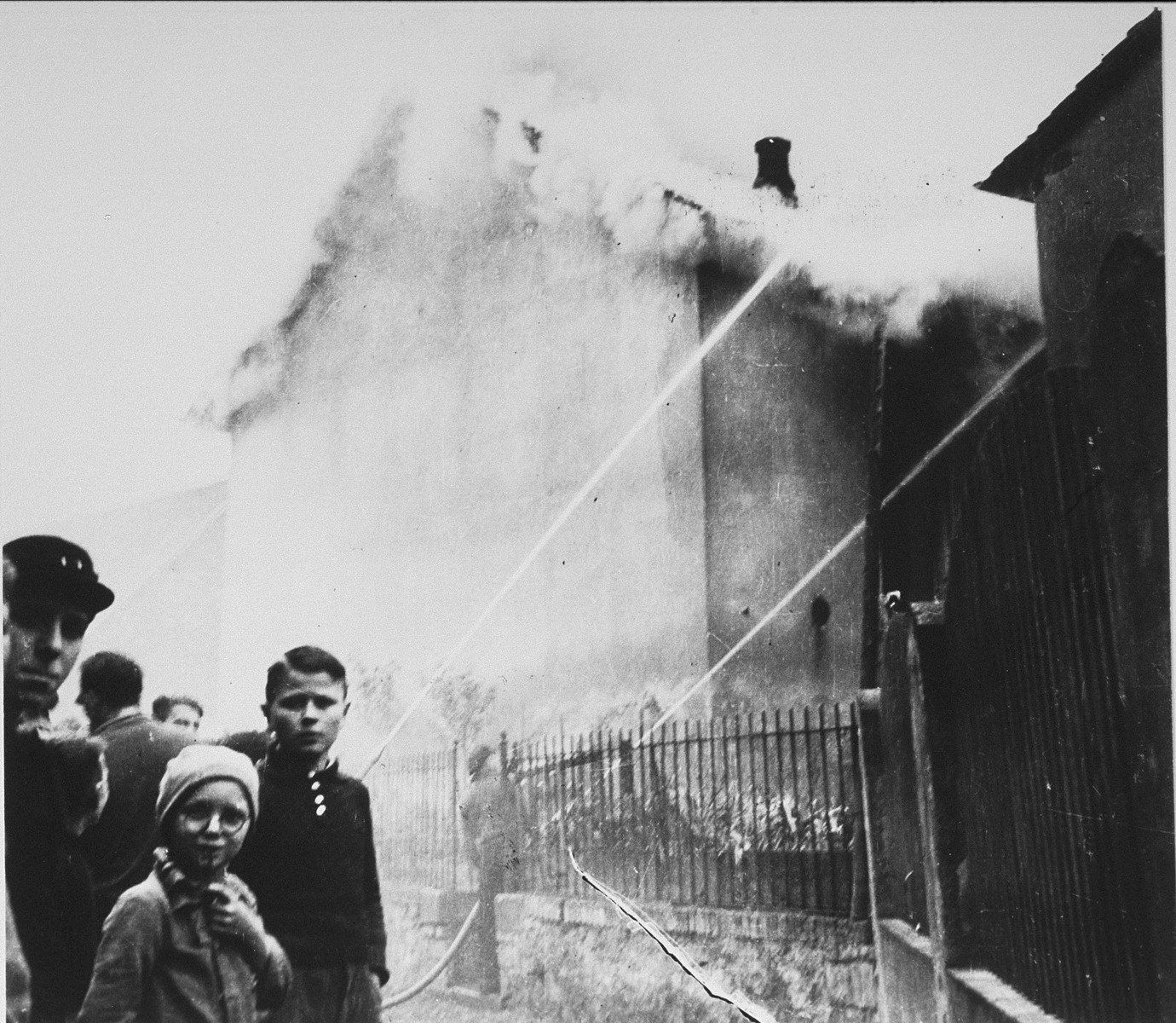 On the morning after Kristallnacht local residents watch as the Ober Ramstadt synagogue is destroyed by fire.     The local fire department prevented the fire from spreading to a nearby home, but did not try to limit the damage to the synagogue.  The youth who took the series of photographs of the burning synagogue in Ober-Ramstadt, Georg Schmidt,  came from a family that opposed the Nazis.  The film was confiscated by police from Schmidt's home the same day the photos were taken, and developed immediately.  The prints and negatives were stored in the city hall until a policeman in the service of the American occupation found them and removed them.  The son-in-law of the policeman found them in a toolbox and donated them to the city archive.