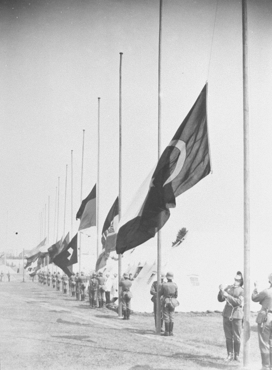 German soldiers raise the flags of nations participating in the 11th Olympiad.