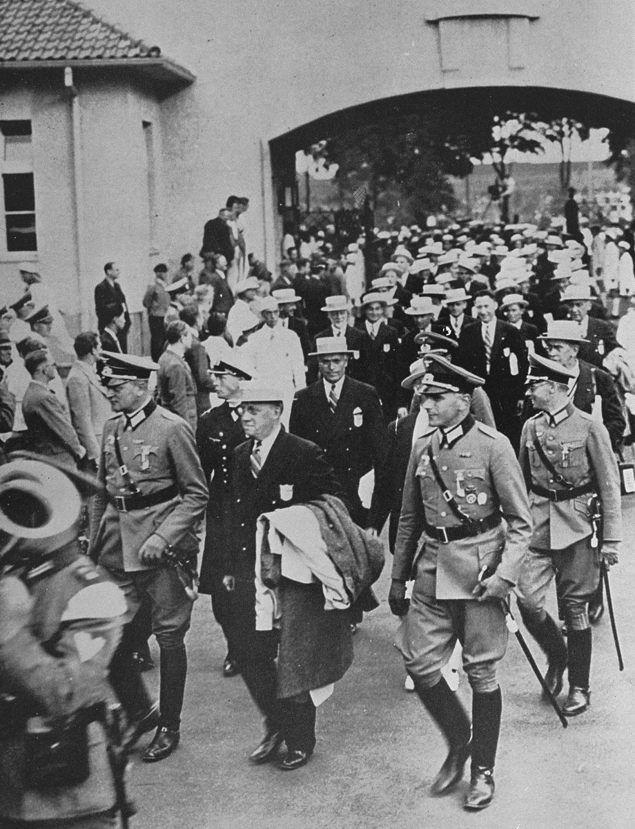 American athletes arrive at the Olympic Village in Berlin.    Avery Brundage, flanked by German officers, is visible at the head of the column.