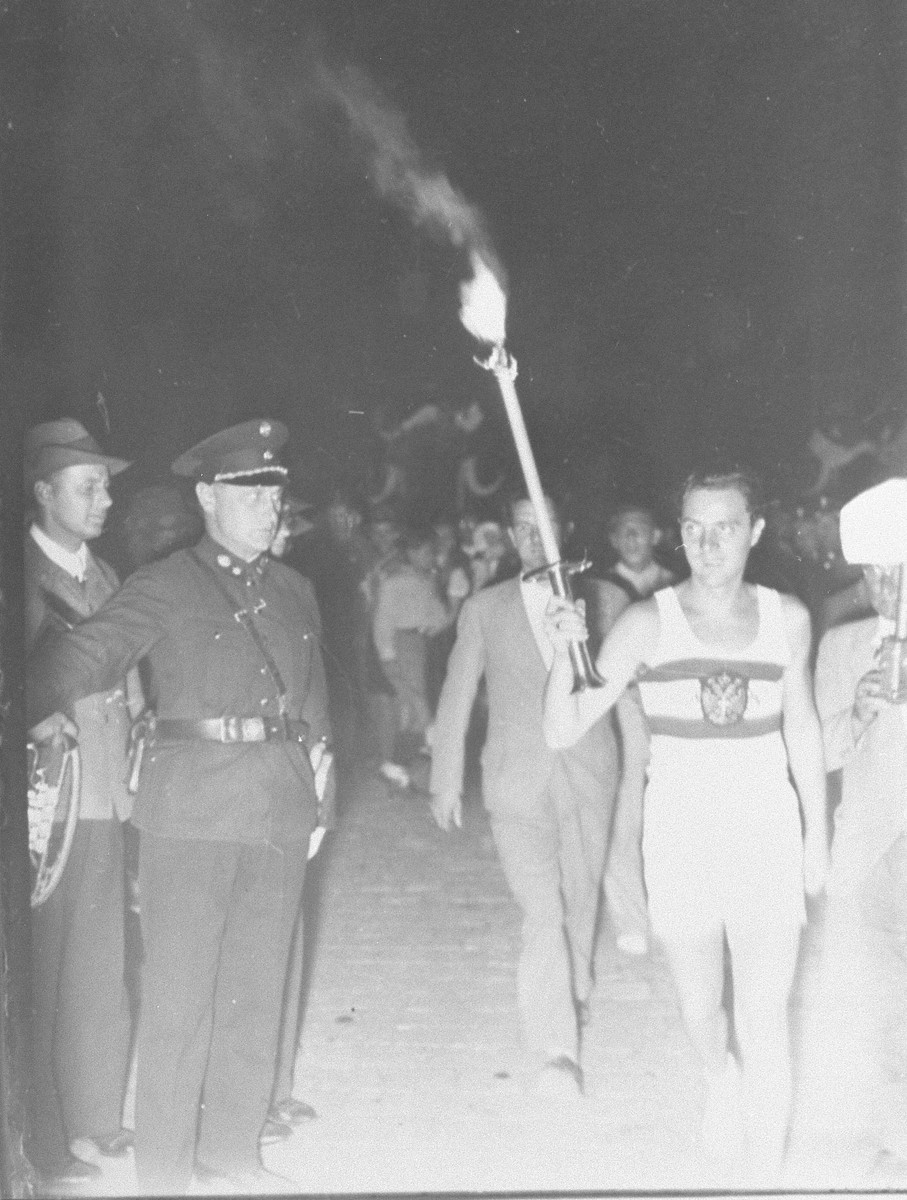 The arrival at the stadium of the runner bearing the Olympic torch.