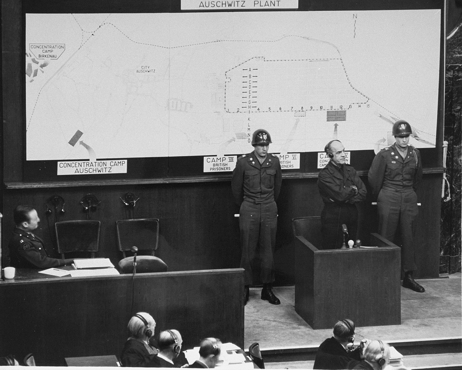 Oswald Pohl testifies on the witness stand during the I.G. Farben Trial in Nuremberg.  Pohl, the former chief of the SS Economic and Administrative Main Office, was convicted by an American Military Tribunal during the Pohl/WVHA Trial in Nuremberg.  While he awaited execution he was called to testify in the I.G. Farben Trial.  To prevent violence or suicide Pohl was handcuffed and flanked by American military guards.  Pohl's testimony confirmed I.G. Farben's use of concentration camp inmates for slave labor.