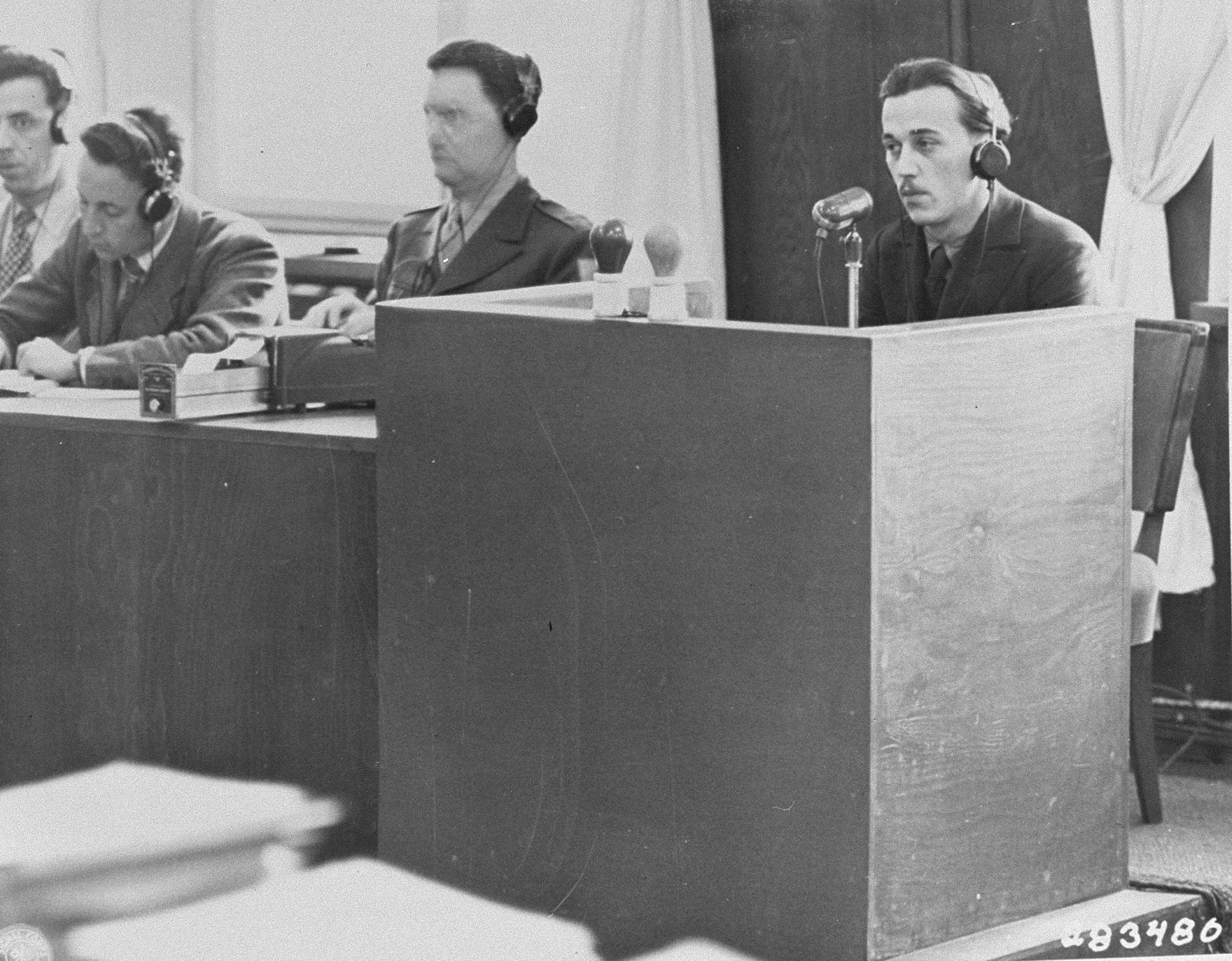 A former Polish inmate of Auschwitz identifies Oswald Pohl while on the stand for the prosecution during the Pohl/WVHA trial.  This took place in a room in the Palace of Justice which was not the main courtroom.