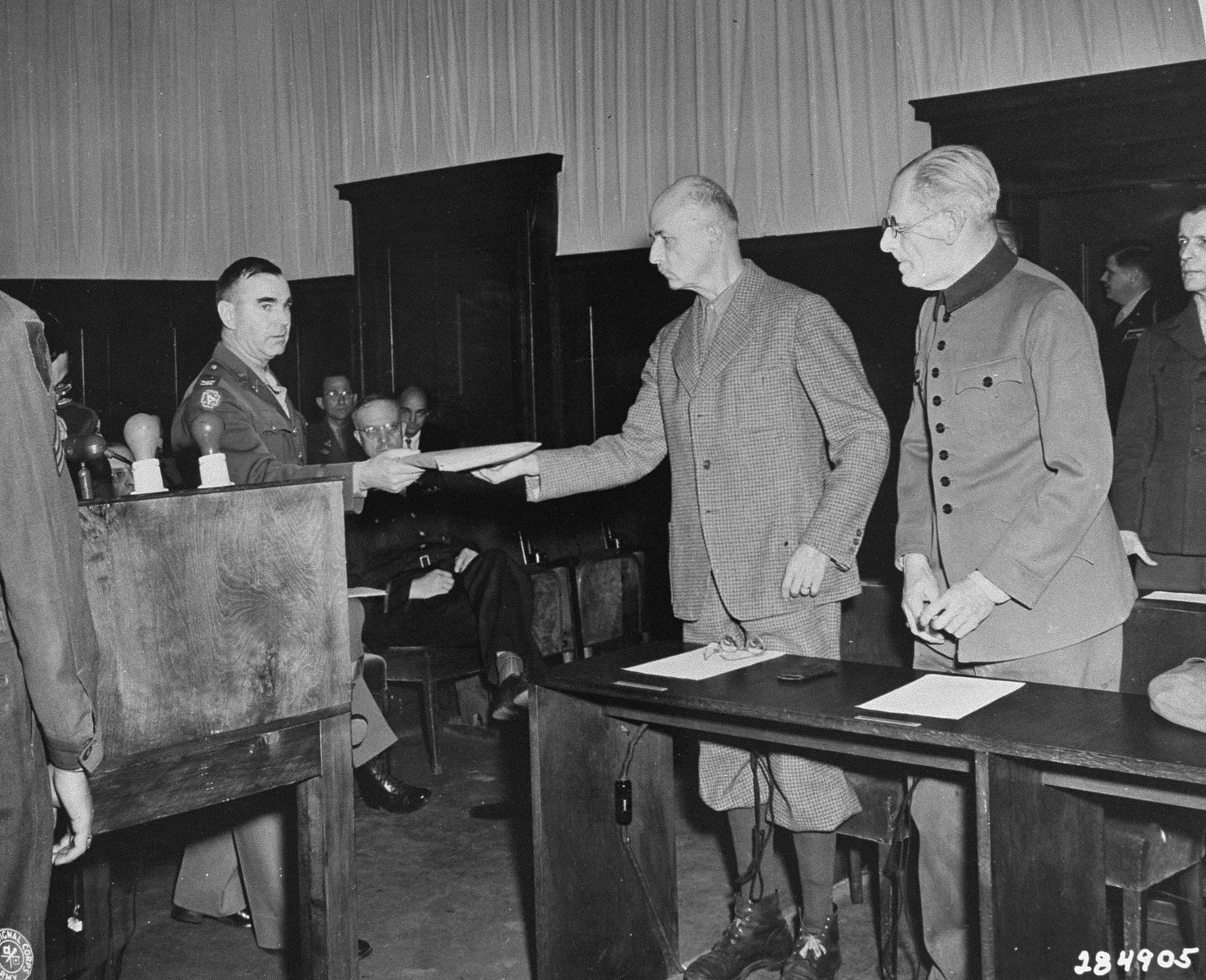 An American military soldier serves Wilhelm List with his indictment at the beginning of the Hostage Case.