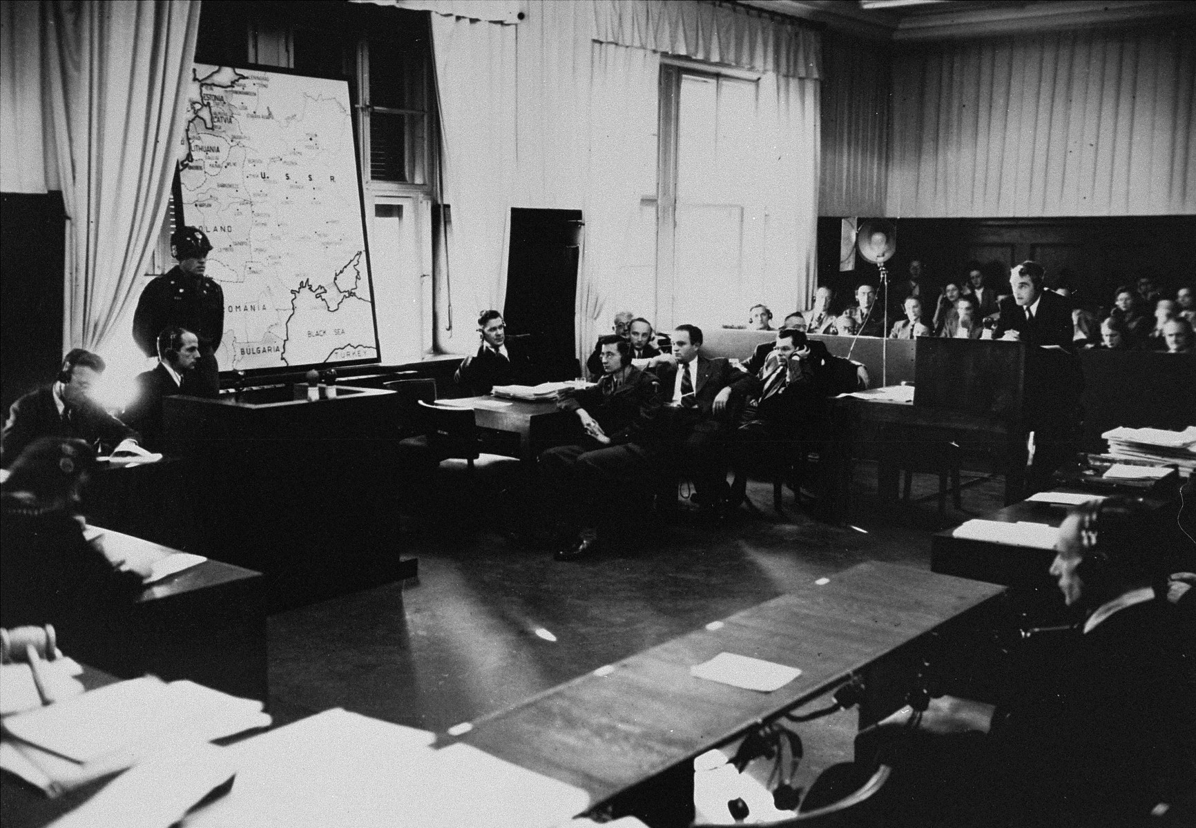 Defendant Dr. Otto Ohlendorf (right) gives testimony in a smaller courtroom in the Palace of Justice during the Einsatzgruppen Trial.