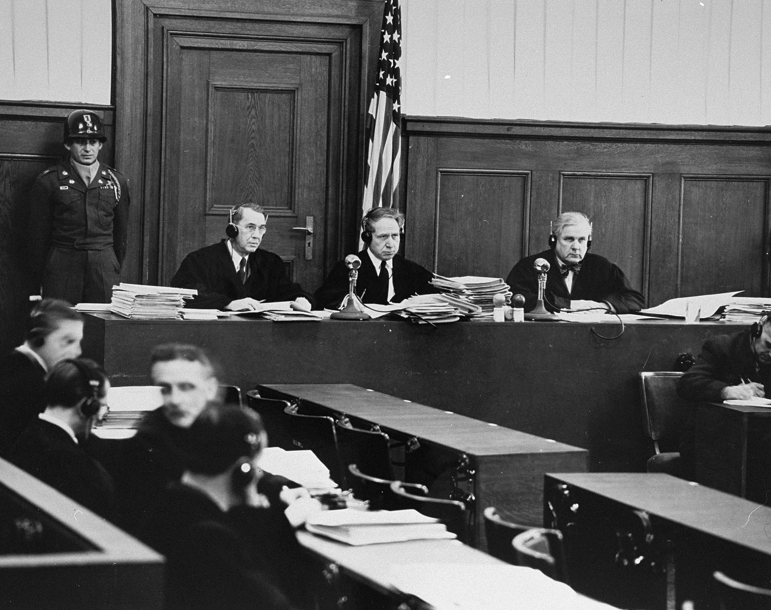 The judges of Military Tribunal II-A, hearing the Einsatzgruppen Trial, in a smaller courtroom in the Palace of Justice.  Pictured left to right are John J. Speight, Michael A. Musmanno, and Richard D. Dixon.