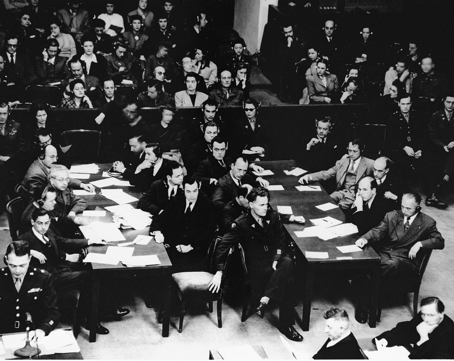 View of the prosecution team during a session of the Medical Case (Doctors') Trial in Nuremberg.    Reading the indictment at the podium (bottom left) is Chief of Counsel Brigadier General Telford Taylor.  Also pictured is Jack W.  Robbins (seated at the left table, second man from the right, facing right).  Seated at the left table, on the left side, from front to back: James M. McHaney, Alexander G. Hardy, Arnost Horlik-Hochwald, and Dr. Leo Alexander.