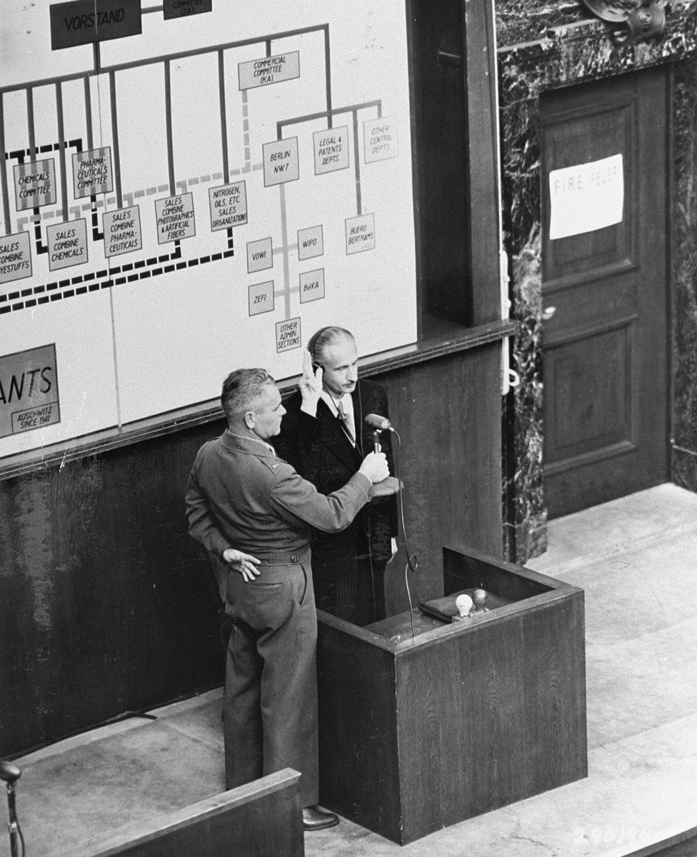 Dr. Hans Wagner, a former researcher for I.G. Farben industries, is sworn in as a witness for the prosecution during the I.G. Farben trial.  A diagram of the organizational structure of I.G. Farben is behind him.