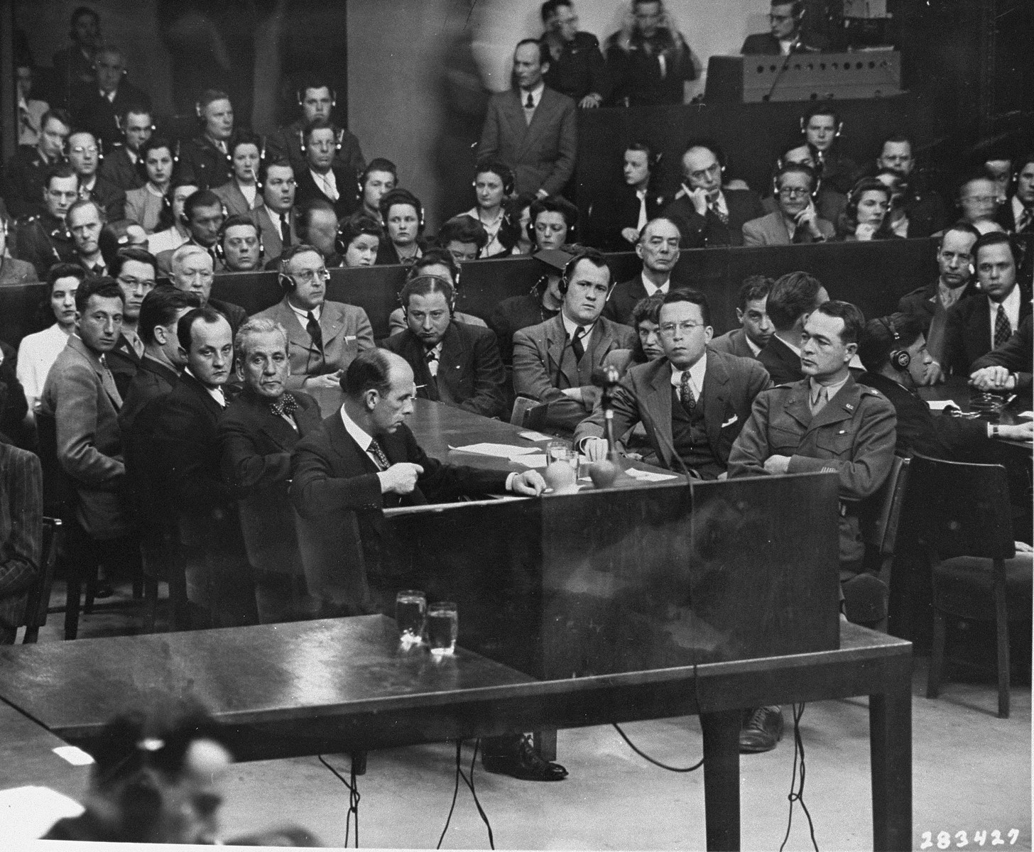 The prosecution team on the day the court announced its findings at the Milch Trial.  Seated at the right is Brigadier General Telford Taylor, Chief of Counsel.  Across from him is Clark Denny, Chief Trial Counsel.  Seated directly in front of the partition, wearing a gray suit, dark tie, and headphones, is Harold Sebring, who presided over the Medical Crial.  On his right is Johnson T. Crawford, another judge for the Medical Crial.  Also seated directly in front of the partition, to the right of the woman wearing a hat, is Walter B. Beals (one of the judges for the Medical Case.""