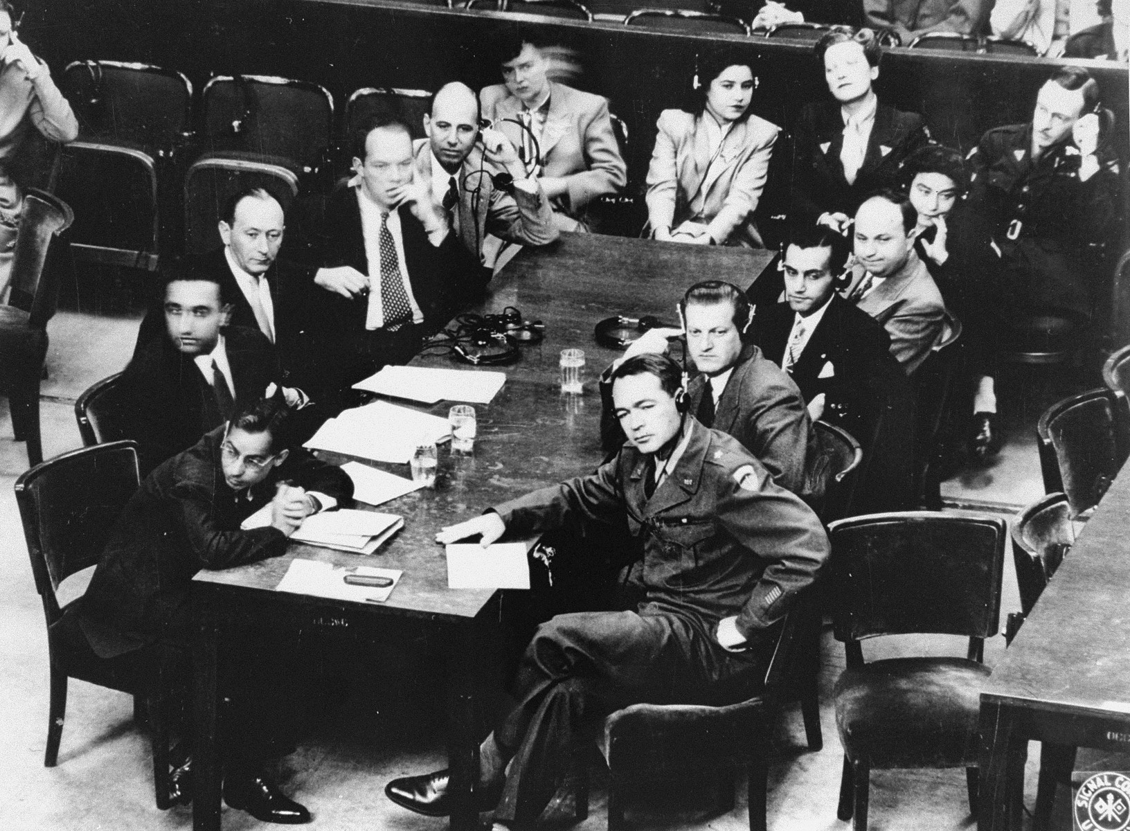 Brigadier General Telford Taylor (front right), Chief of Counsel for War Crimes, sits at the prosecution table with his staff during the reading of the charges against the defendants in the RuSHA Trial.