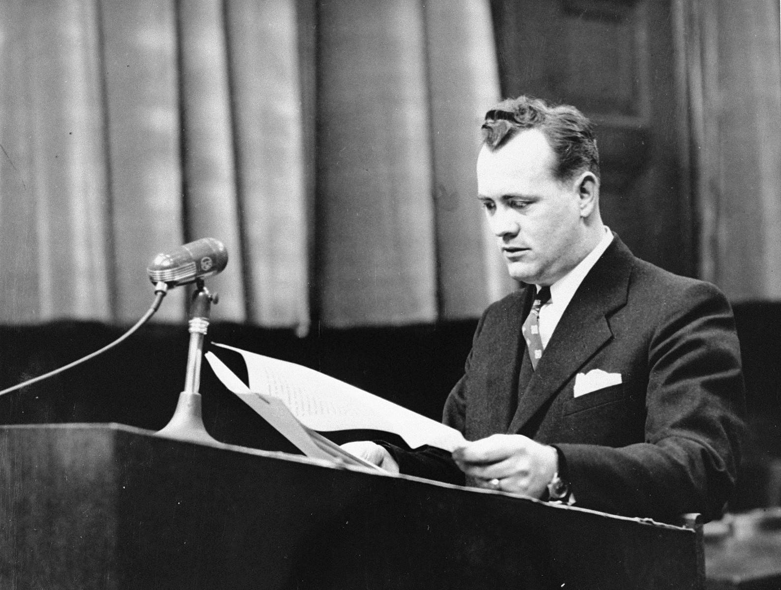 Alexander G. Hardy, Associate Counsel for the Prosecution, stands at the speaker's podium during a session of the Medical Case (Doctors') Trial in Nuremberg.