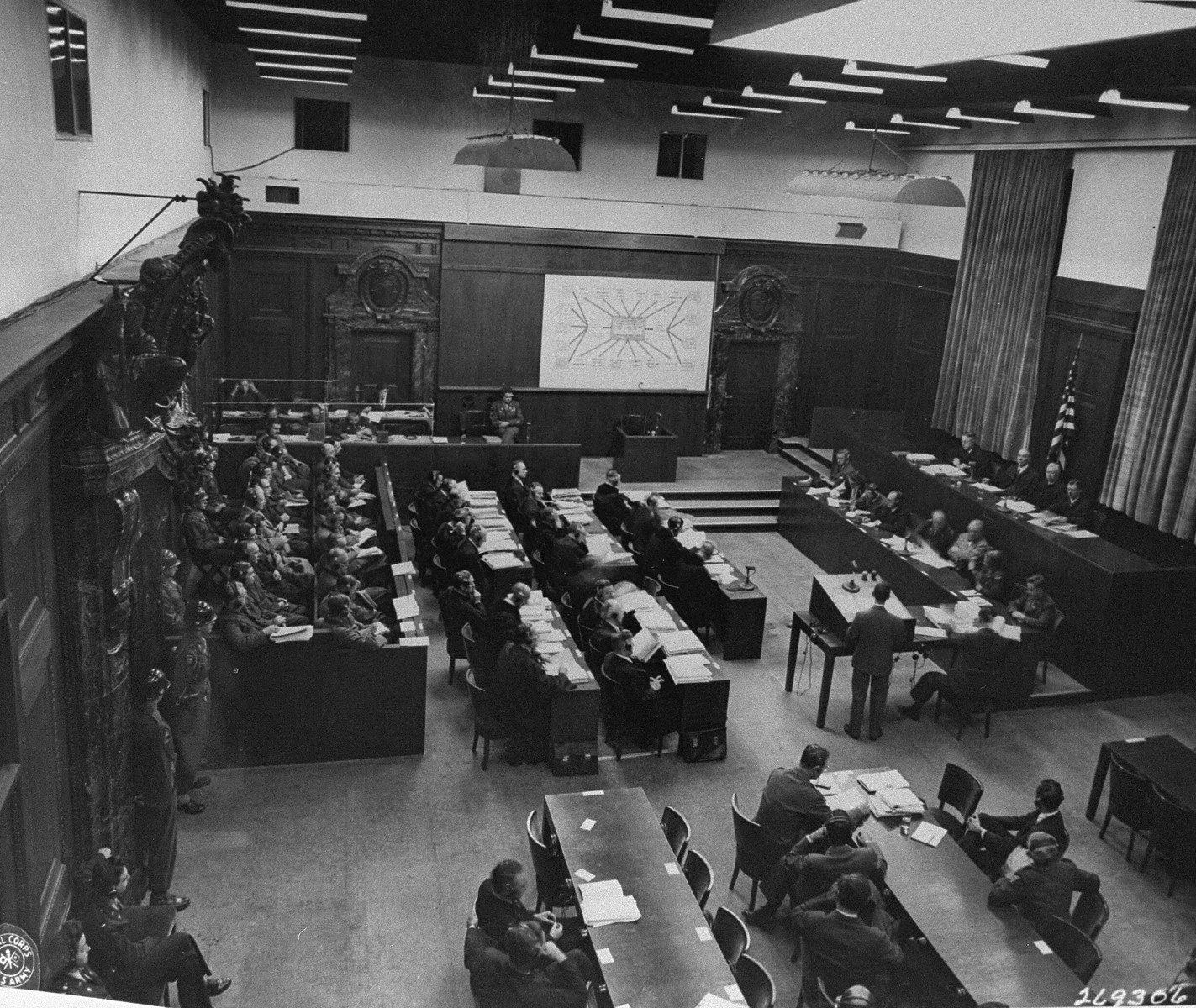 The defendants (left), their lawyers (center), the Military Tribunal I (right), and the prosecution (bottom), listen to the proceedings at a session of the Medical Case (Doctors') Trial in Nuremberg.