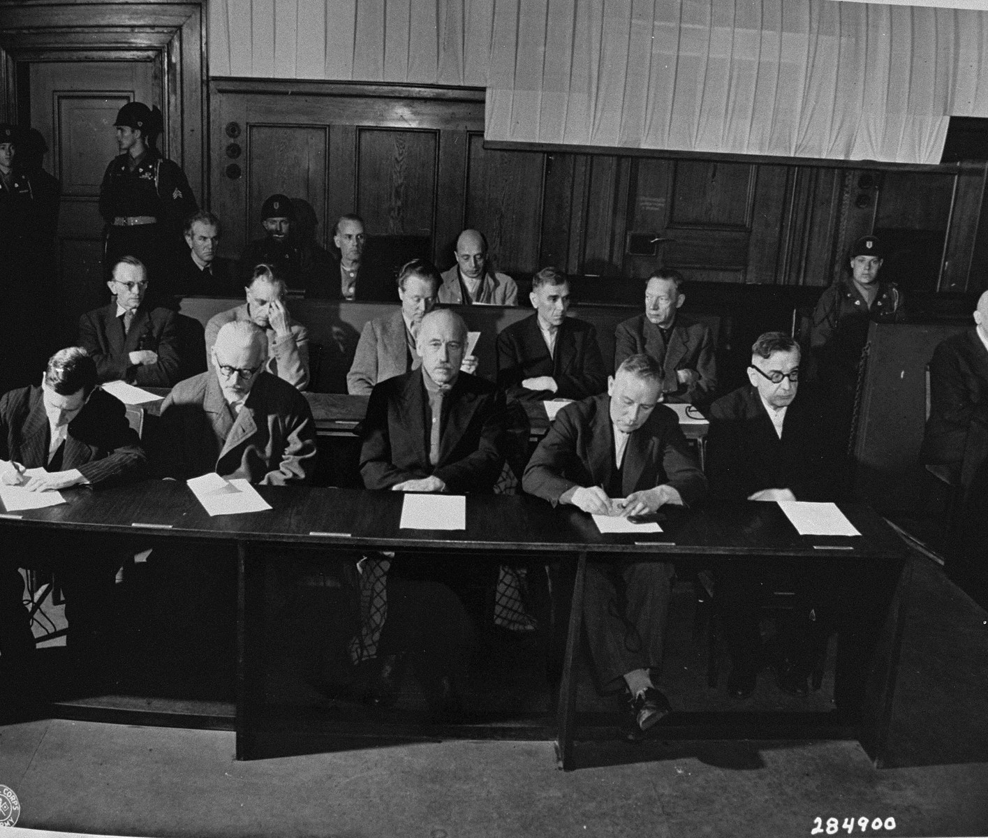 The defendants in the I.G. Farben Trial hear the indictments against them.  This took place in a room in the Palace of Justice which was not the main courtroom.
