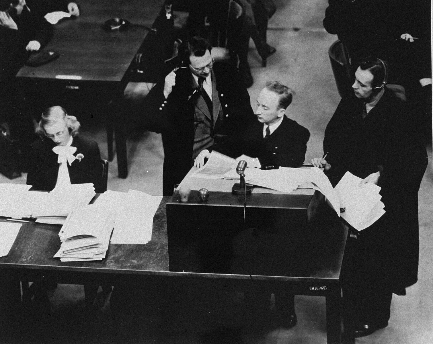 Chief prosecutor Benjamin Ferencz presents documents as evidence at the Einsatzgruppen Trial.    Ferencz is flanked by German defense lawyers, Dr. Friedrich Bergold (right, counsel for Ernst Biberstein) and Dr. Rudolf Aschenauer (left, counsel for Otto Ohlendorf), who are protesting the introduction of the documents as evidence.