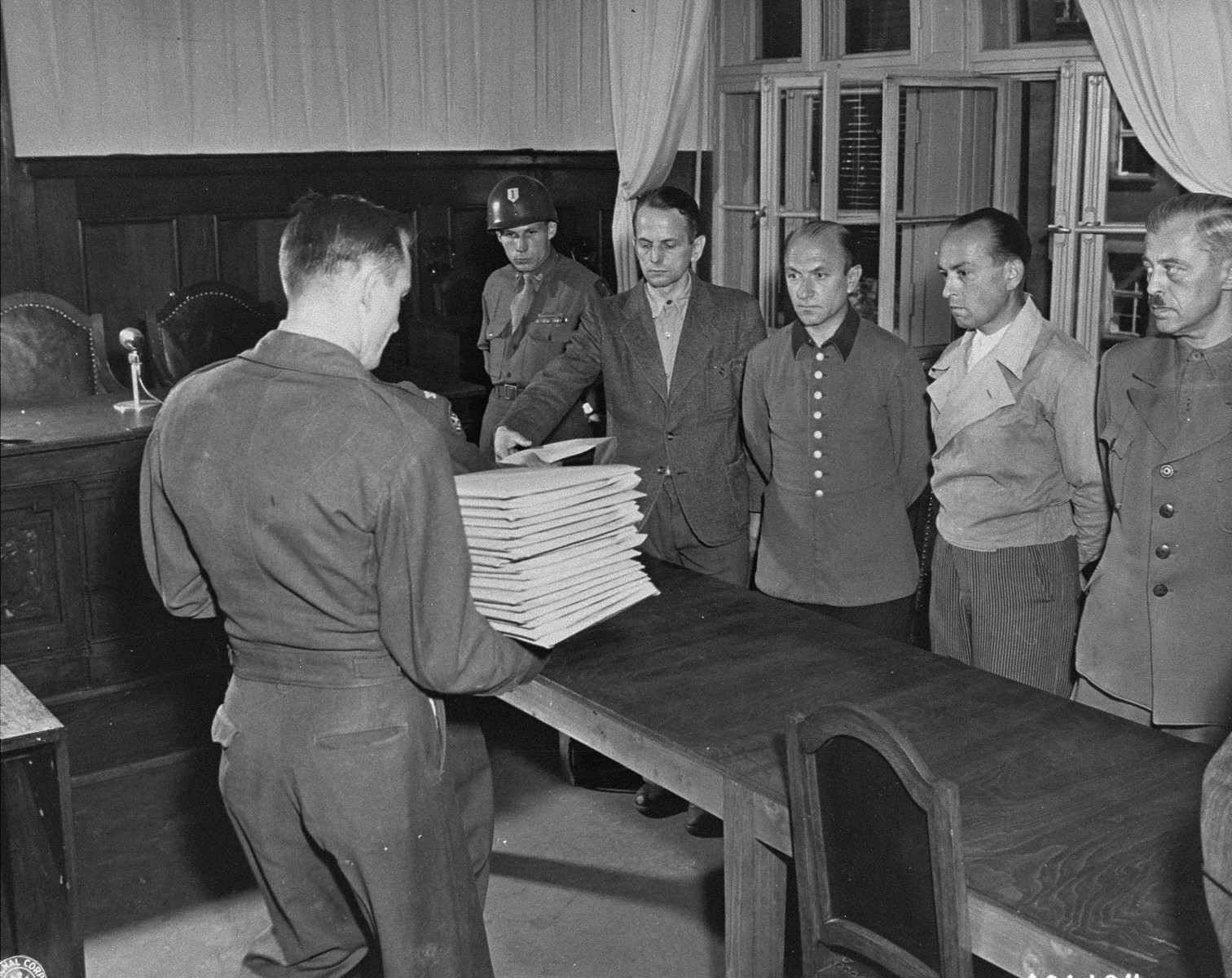 Defendant Otto Ohlendorf (left) receives his indictment from Col. C.W. Mays, Marshal of the Military Tribunal, before the Einsatzgruppen Trial.  The other defendants (left to right) are, Heinz Jost, Erich Naumann, and Erwin Schulz.