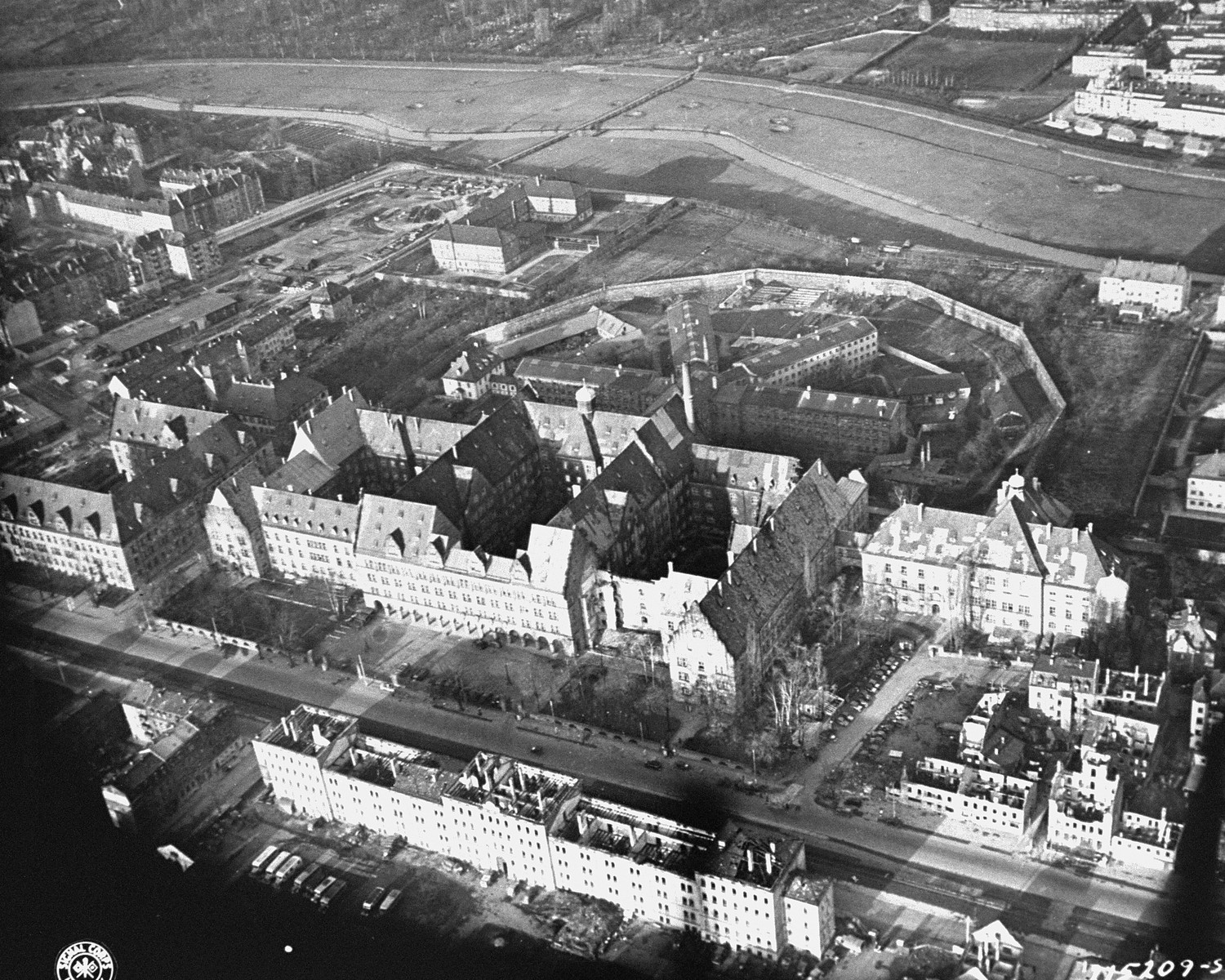 Aerial view of the Nuremberg Palace of Justice and prison, where the war crimes trial of the International Military Tribunal was held and its defendants incarcerated.    In the foreground is the Palace of Justice.  The structure on the right that is connected to the the main building by a passageway, is the location of the actual courtroom.  The main part of the Palace of Justice housed the offices of those working on the IMT.  In the background are the four wings of the Nuremberg prison.  The IMT defendants were housed in the far right wing; the witnesses in the left wing; and other prisoners in the two center wings.