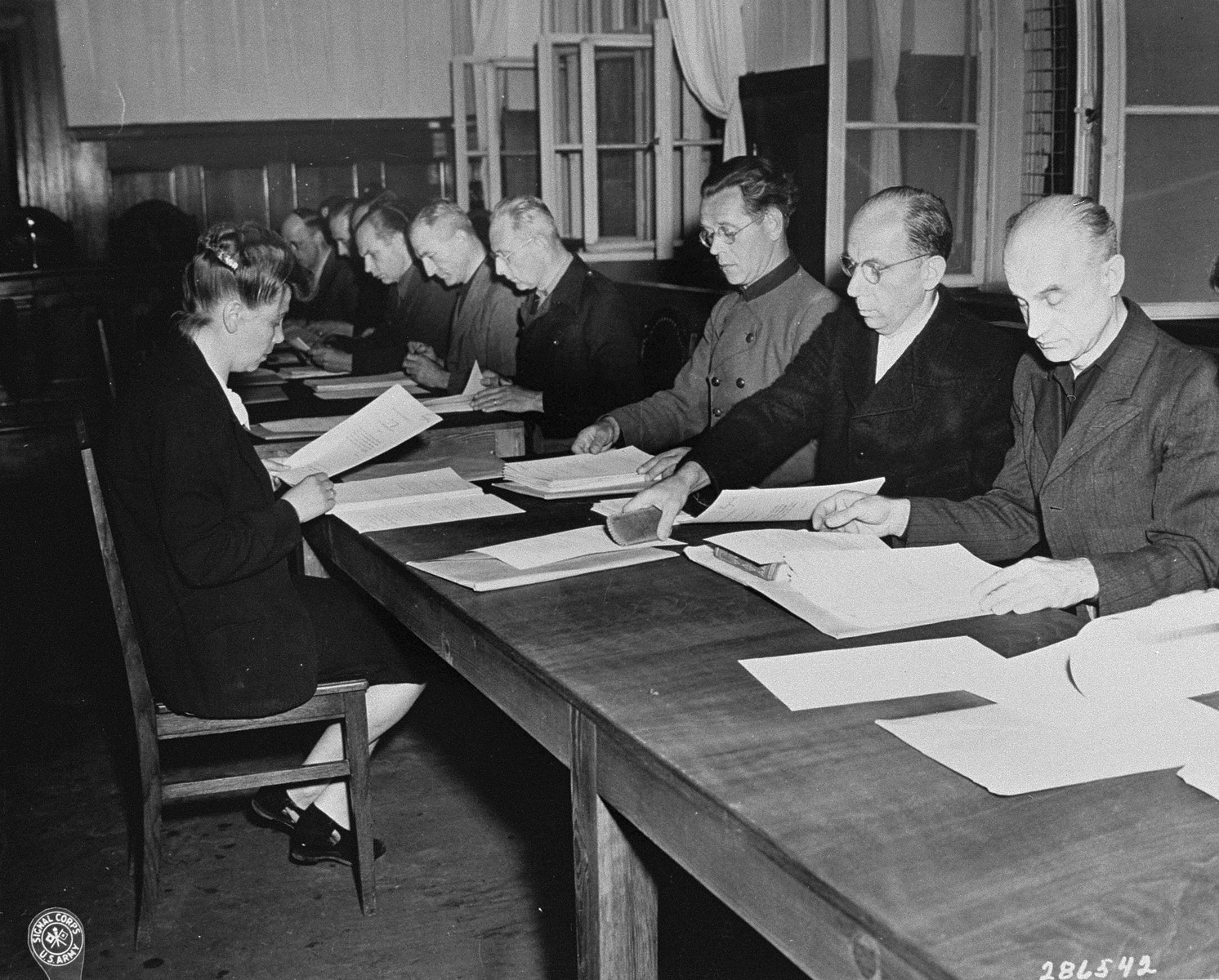 The fourteen defendants read the indictments against them at the RuSHA Trial.