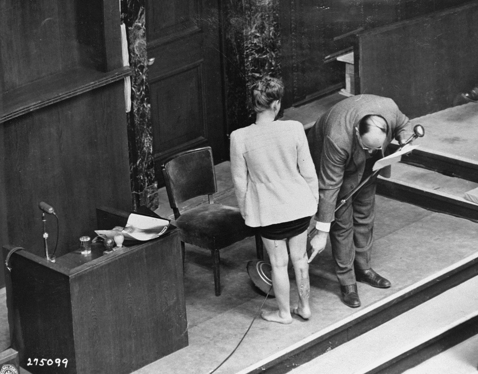 Polish survivor Jadwiga Dzido shows her scarred leg to the court, while expert witness Dr. Alexander explains the nature of the medical experiment performed on her in the Ravensbrueck concentration camp.  Dzido and Alexander were appearing as witnesses at the Doctors Trial.  The experiments were performed by defendants Herta Oberheuser and Fritz Ernst Fischer, on November 22, 1942.