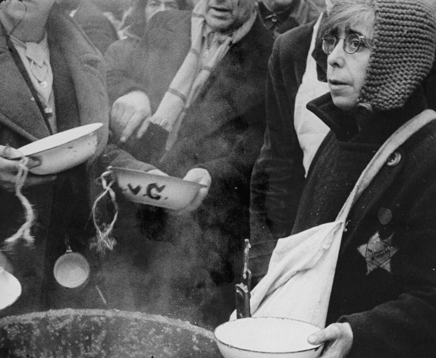 A woman who has just arrived in Theresienstadt with a transport of Dutch Jews waits to receive her bowl of  food in the courtyard of the ghetto. [oversized photo]