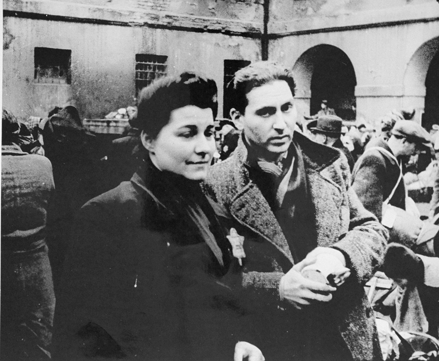 A couple who has just arrived in Theresienstadt with a transport of Dutch Jews waits in the main courtyard of the ghetto. [oversized photo]