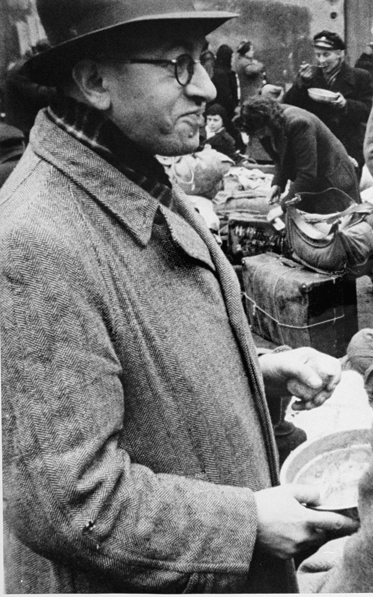 A man who has just arrived in Theresienstadt with a transport of Dutch Jews receives a bowl of food in the main courtyard of the ghetto.  [oversized photo]