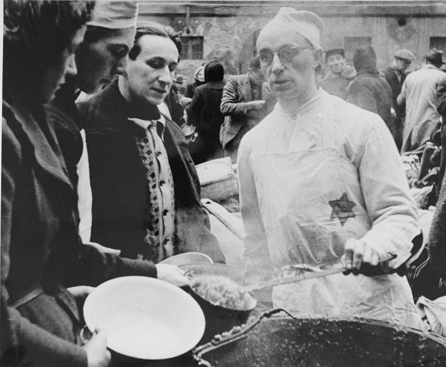 A prisoner wearing a cook's uniform doles out food in the ghetto courtyard to prisoners who have just arrived in Theresienstadt with a transport of Dutch Jews.  [oversized photo]   The man serving soup is possibly Karel Arnstein.