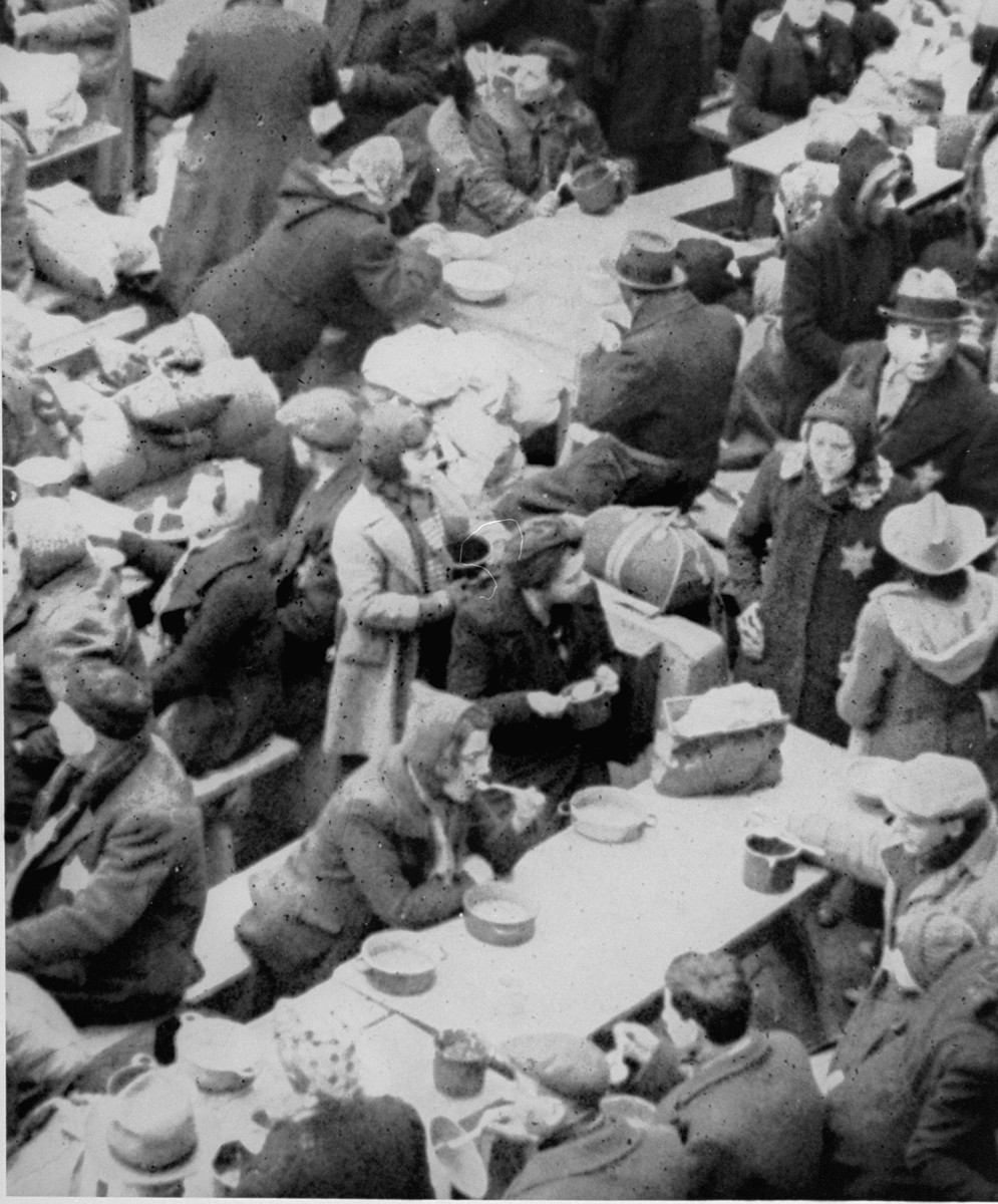 View from above of members of a transport of Dutch Jews who have just arrived in Theresienstadt, eating their first meal in the courtyard of the ghetto.  [oversized photo]