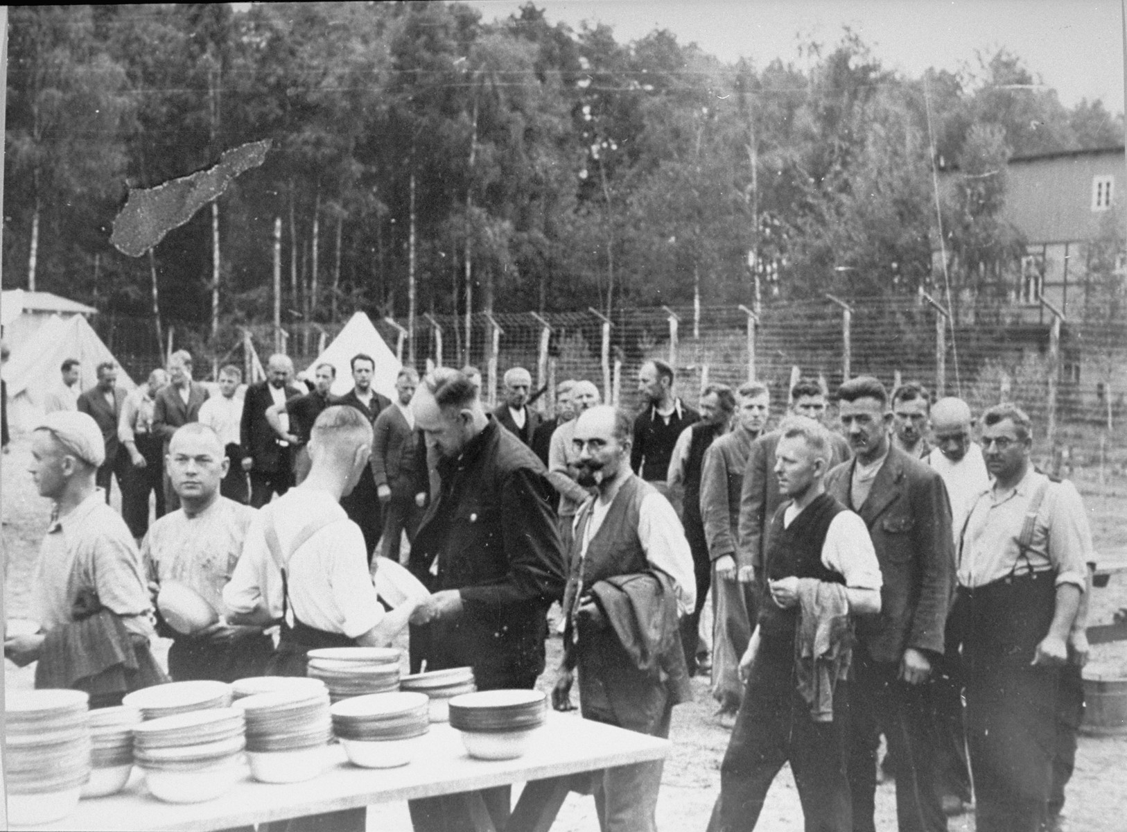 Prisoners involved in the construction of the camp queue up for food.