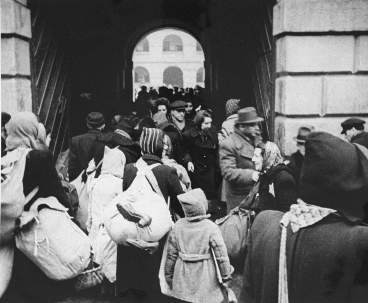 A large group of Dutch Jews who have just arrived in Theresienstadt are herded through a stone archway into the camp. [oversized photo]