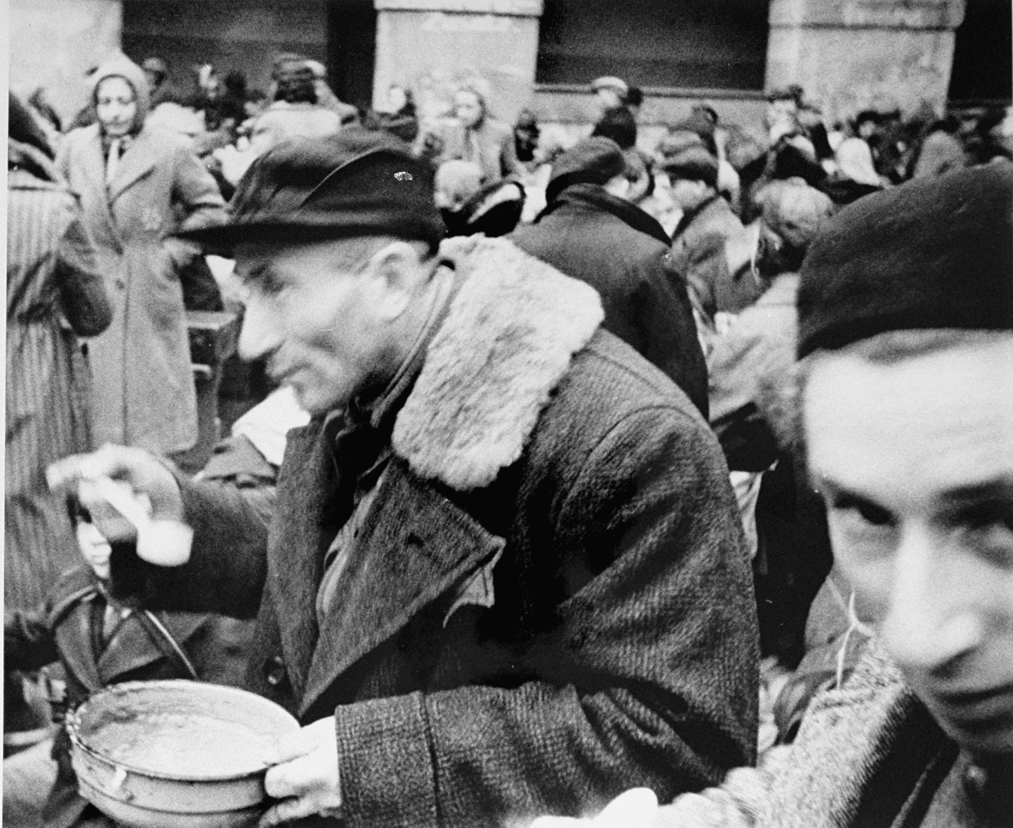 A man who has just arrived in Theresienstadt with a transport of Dutch Jews eats from a bowl in the main courtyard of the ghetto. [oversized photo]