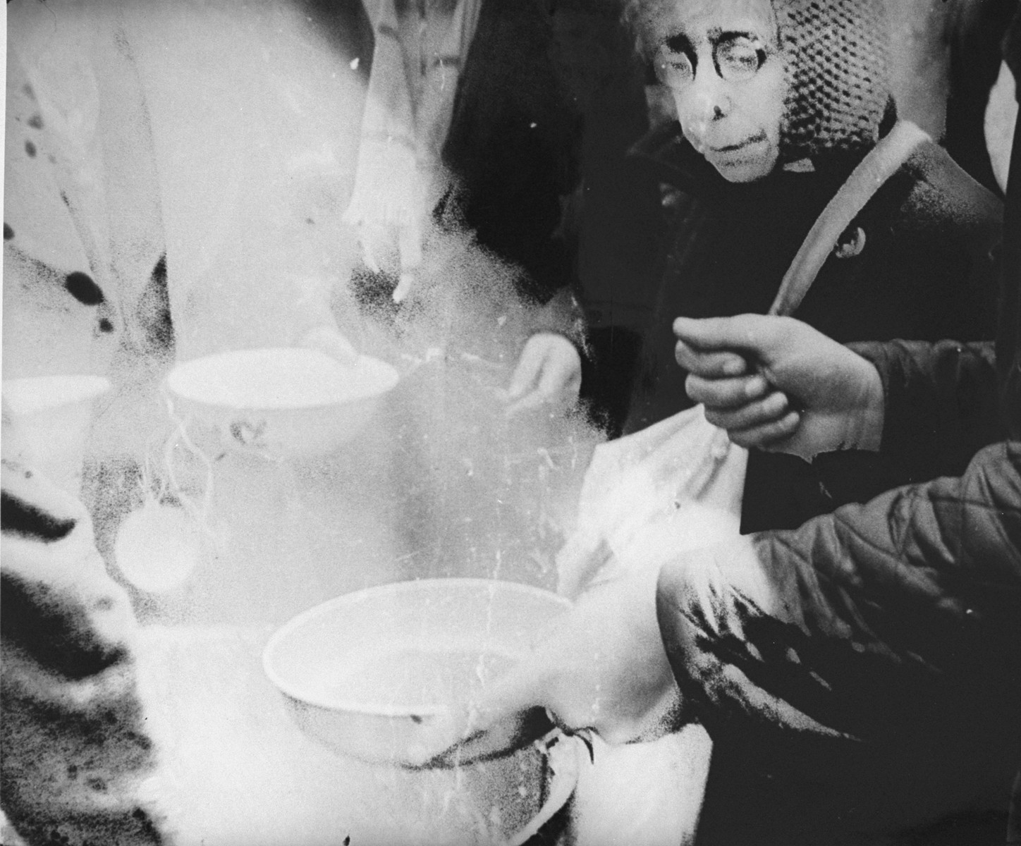 An elderly woman who has just arrived in Theresienstadt with a transport of Dutch Jews receives a bowl of soup. [oversized photo]