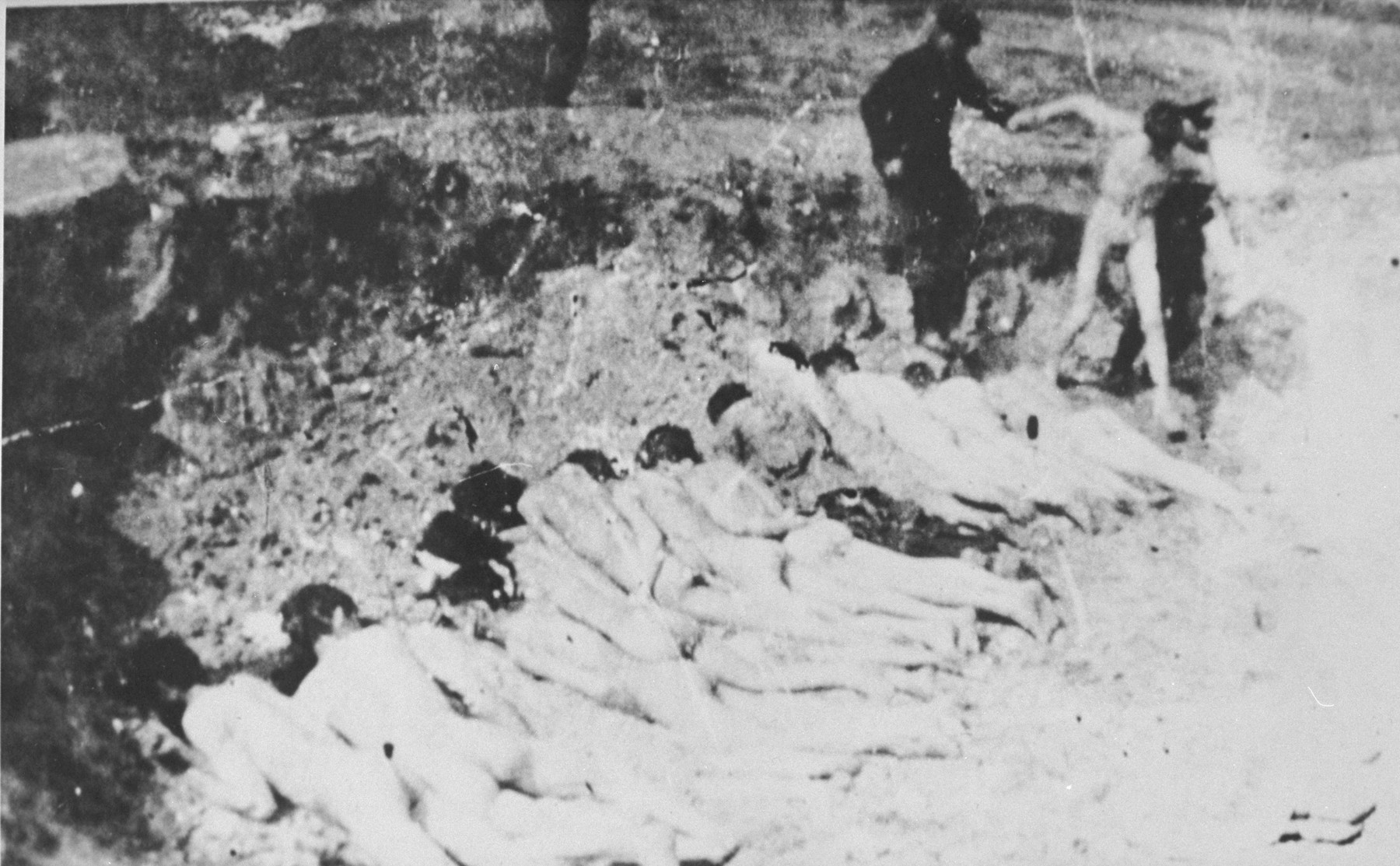 A naked prisoner is led to an execution site, possibly at Ponary, where others either have been shot already or forced to lie face down prior to being shot.