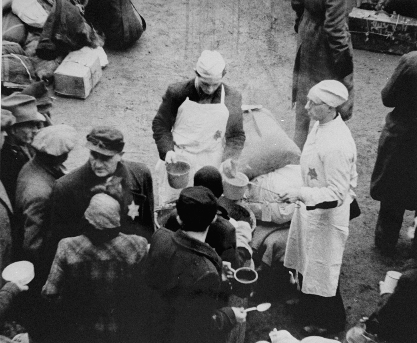 View from above of a prisoner wearing a cook's uniform doling out food in the ghetto courtyard to prisoners who have just arrived in Theresienstadt with a transport of Dutch Jews.  [oversized photo]   The man on the right serving soup is possibly Karel Arnstein.