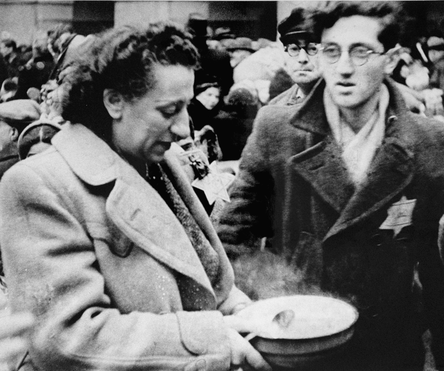 A woman who has just arrived in Theresienstadt with a transport of Dutch Jews holds a bowl of soup in the main courtyard of the ghetto. [oversized photo]