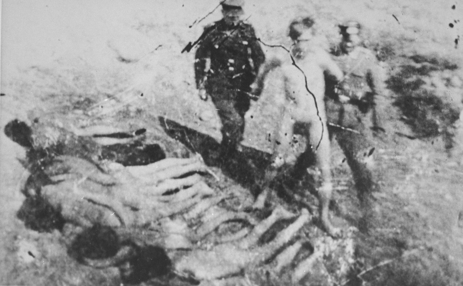 A naked prisoner is led to an execution site, possbily Ponary, where others either have been shot already or forced to lie face down prior to being shot.