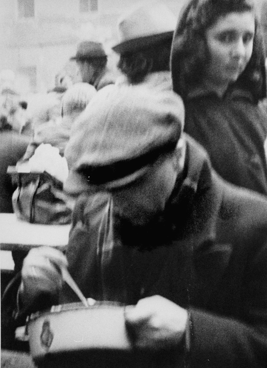 A man who has just arrived in Theresienstadt with a transport of Dutch Jews eats from a bowl in the courtyard of the ghetto.  [oversized photo]