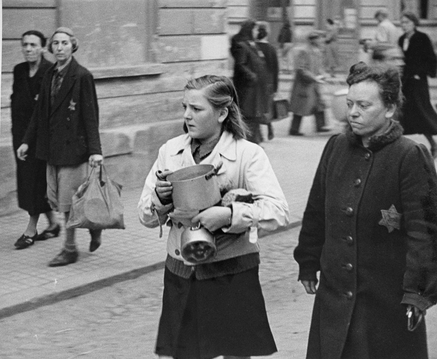 A teenage girl carries two small pots along a street in Theresienstadt.  Some of the Jews pictured appear to be new arrivals. [oversized photo]