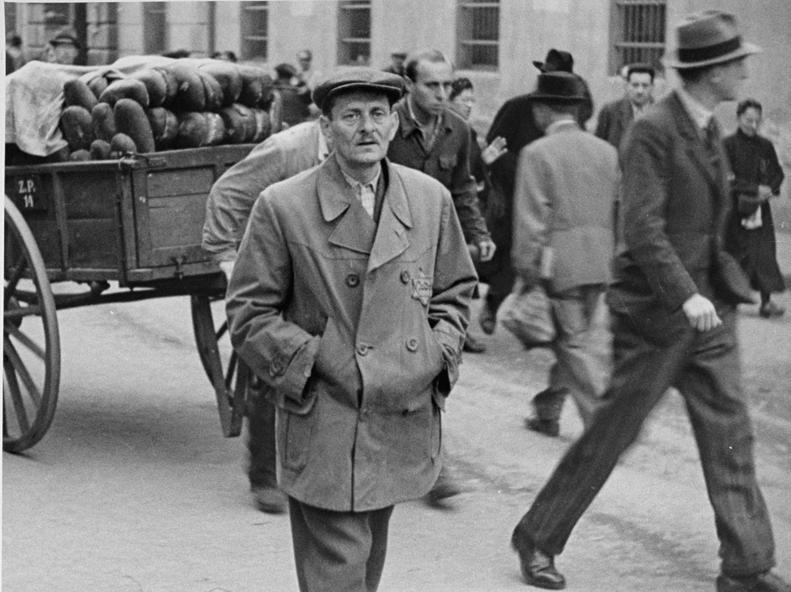 A Jew wearing a yellow star walks along a street in Theresienstadt just ahead of a man pulling a wagon of bread. [oversized photo]
