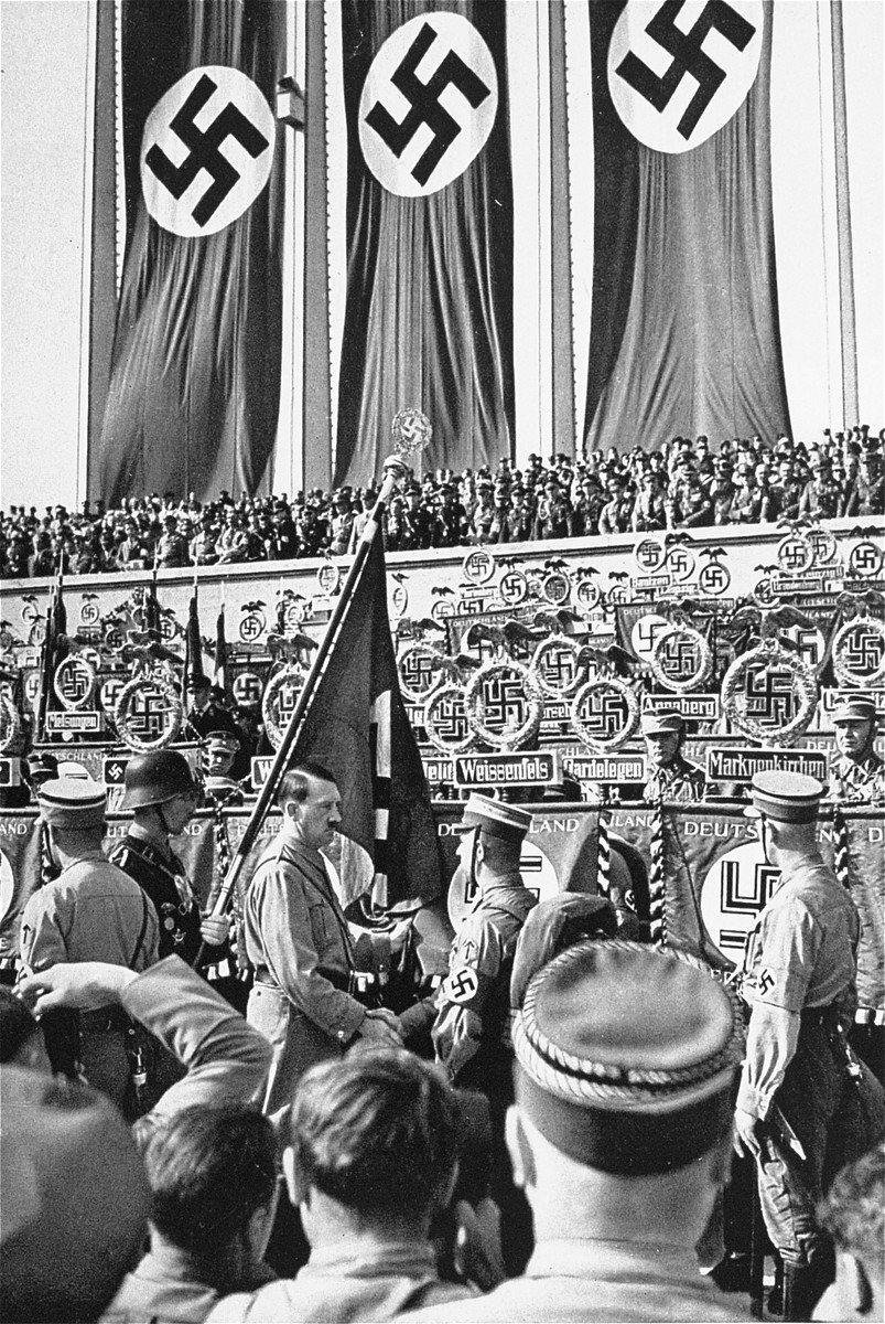 """Adolf Hitler greets an SA officer at a Reichsparteitag (Reich Party Day) ceremony while clutching the party's """"Blood Banner,"""" which was supposedly stained with the blood of National Socialists killed during the Munich Putsch in 1923."""