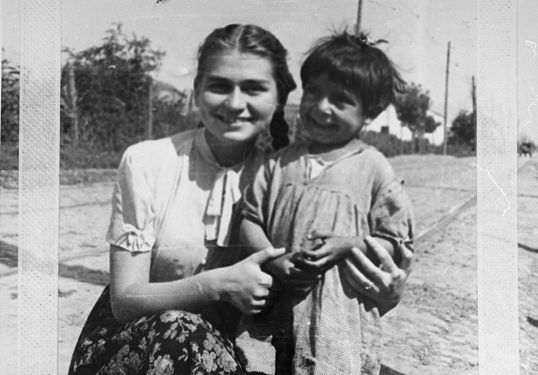 The photographer's sister poses with a Romani) Gypsy child in hiding during the German occupation.
