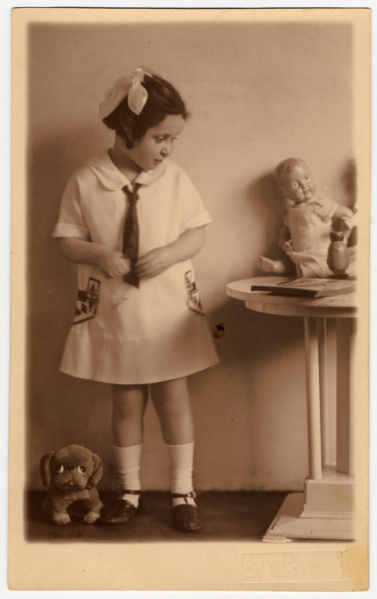 Studio portrait of a young Jewish girl with a doll and stuffed animal.  Pictured is Margit Morawetz.