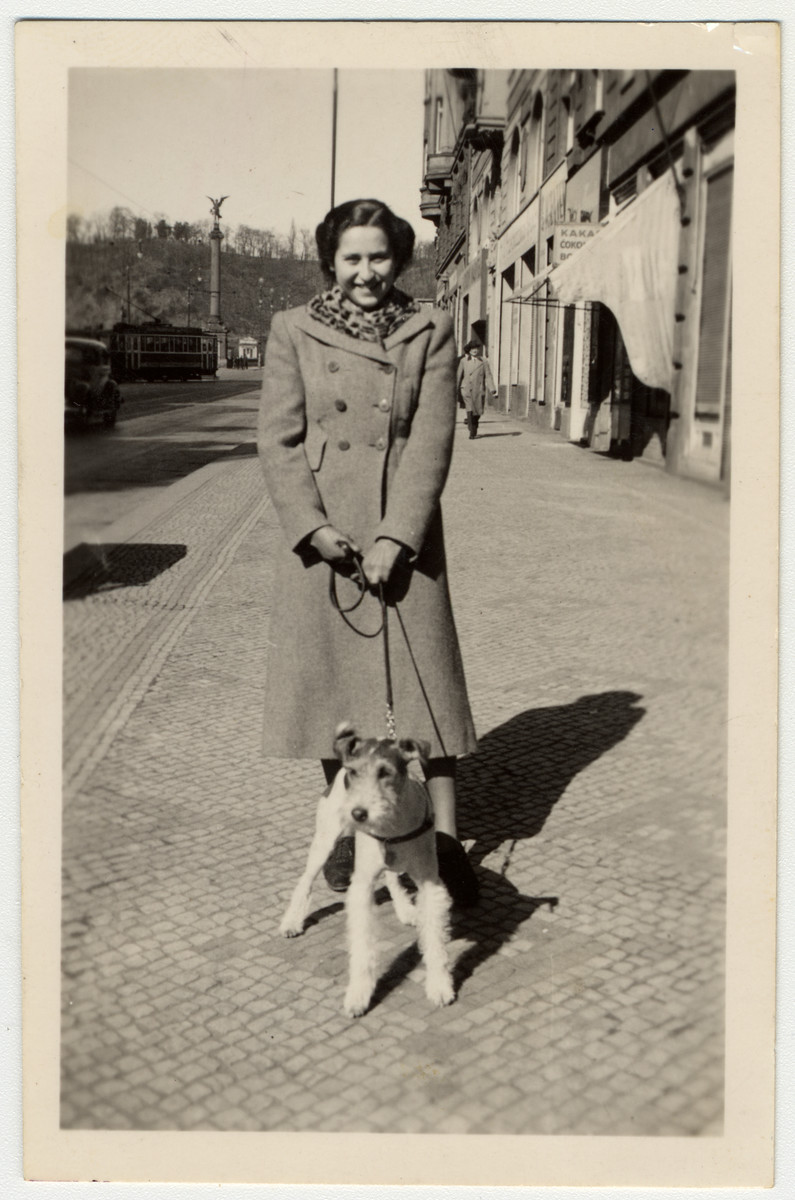 A Jewish teenage girl walks her dog on a street in Prague.  Pictured is Margit Marowetz.