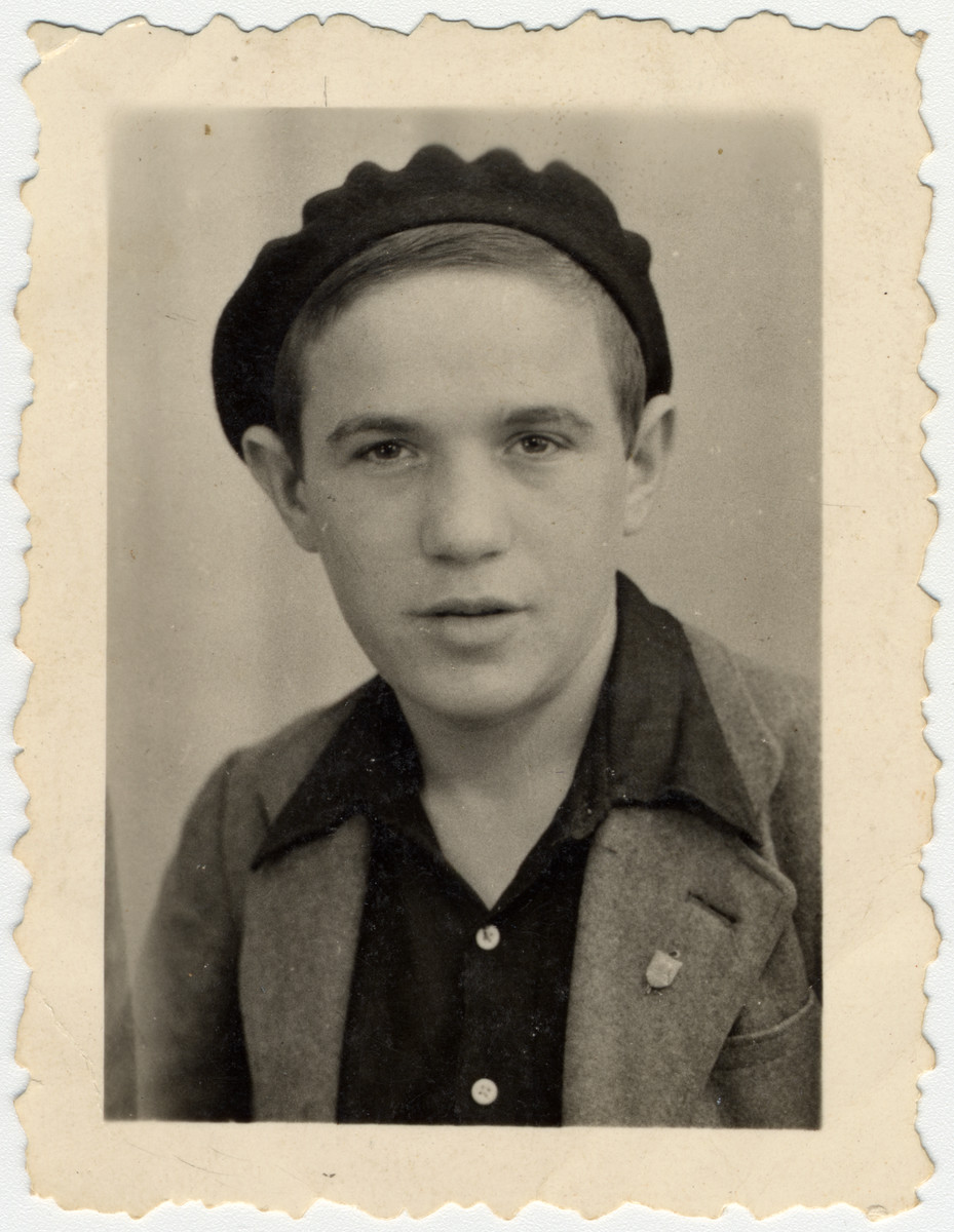 Studio portrait of a Buchenwald Boy [probably in Ambloy] wearing a beret.