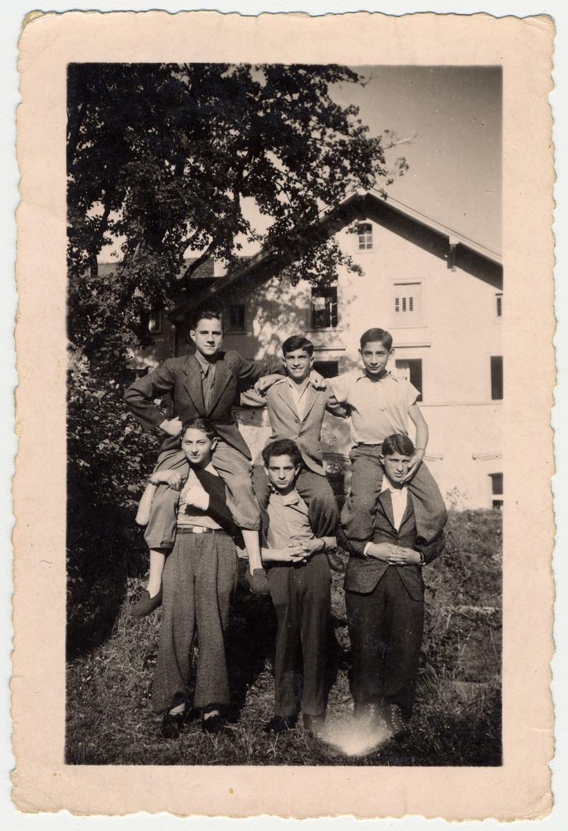 Six teenagers, among them child survivors from Buchenwald, make a human pyramid in [what probably is] the Ambloy children's home.  Among them is Szimon Mirawnik