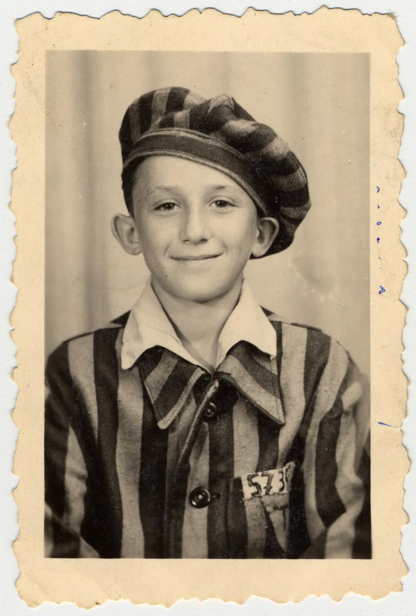 "Studio portrait of Buchenwald survivor, Heniek Kaliksztajn wearing a prisoner uniform.  Heniek Kaliksztajn was born on June 9, 1931 in Strzemieszyce.  The photo is inscribed to ""my friend Berek"". he children went to to a photo studio in town asking for a portrait of themselves in uniform."